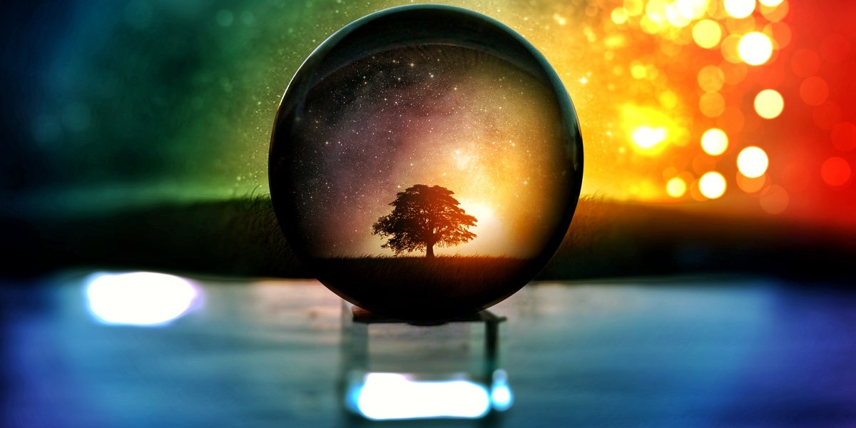 Crystal ball resting on stand, with water in the background.